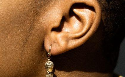 African American lady's ear. Why can't I hear yu God?